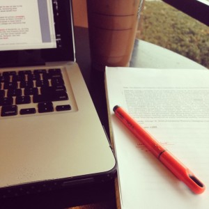 A laptop showing a word document, an essay manuscript with a highlighter on top, and a cup of coffee sitting on table.